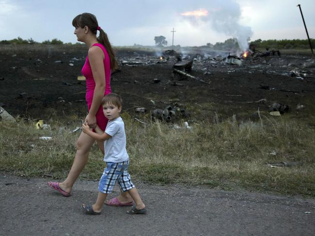 A woman with a child walks past the crash site of a passenger plane near the village of Hrabove, Ukraine. Picture: AP