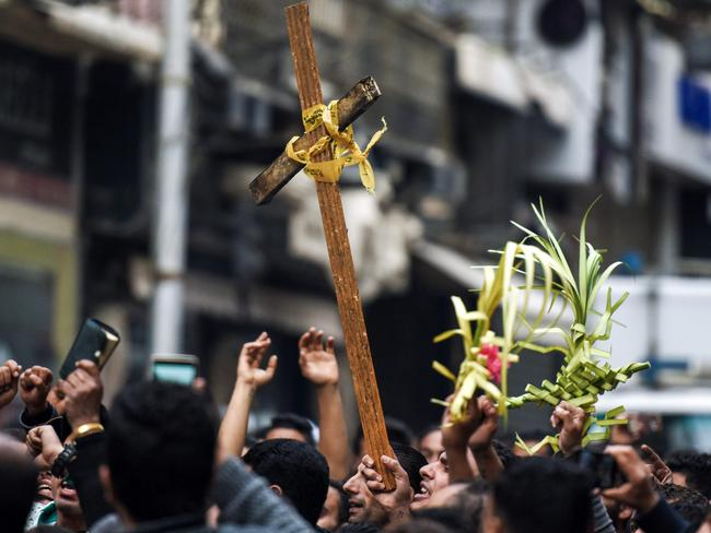 Egyptians raise a wooden cross and palm leaves originally intended for Palm Sunday celebrations, as they gather outside the Coptic Orthodox Patriarchate in Alexandria after the bomb blasts. Picture: AFP/Mohamed El-Shahed