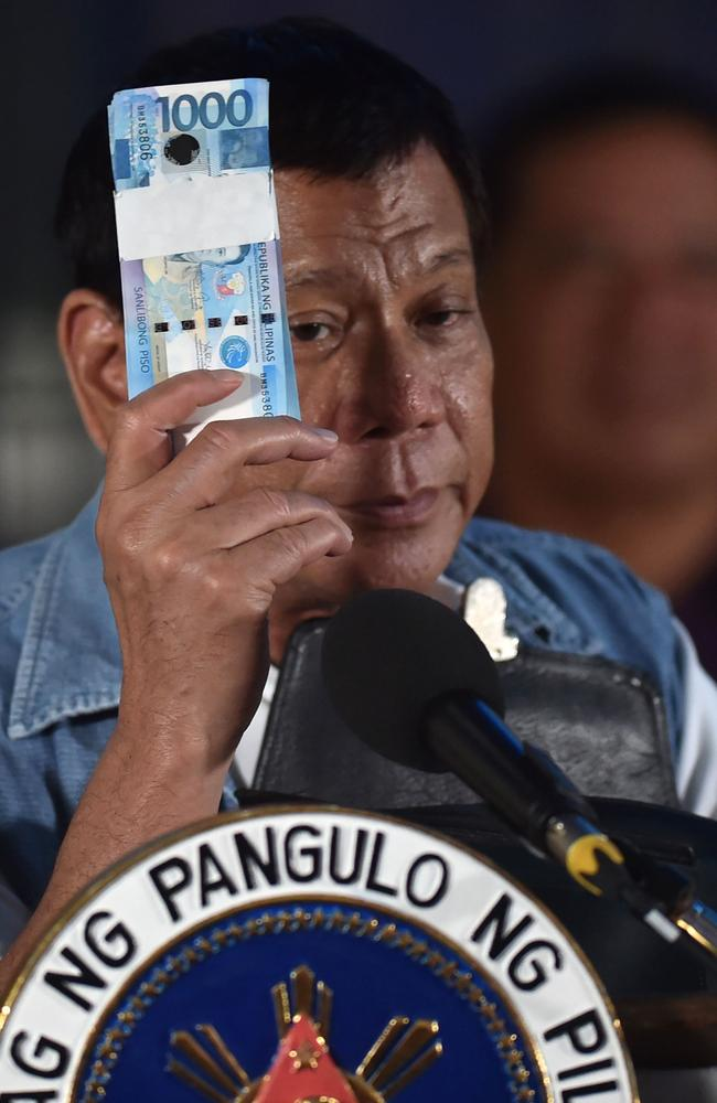 Philippines' President Rodrigo Duterte holds a wad of peso bills, which he later gave to evacuees from Marawi, while speaking to them in Iligan on the southern island of Mindanao. President Rodrigo Duterte apologised for aerial bombings that have destroyed a large part of the Philippines' main Muslim city but said it was necessary to crush self-styled Islamic State followers. Picture: Ted Aljibe
