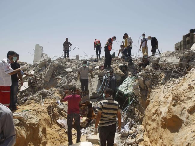 Devastation ... rescue workers search for victims on July 30, 2014 amid the rubble of a building destroyed by an Israeli air strike in Rafah in the southern Gaza Strip. Picture: Said Khatib