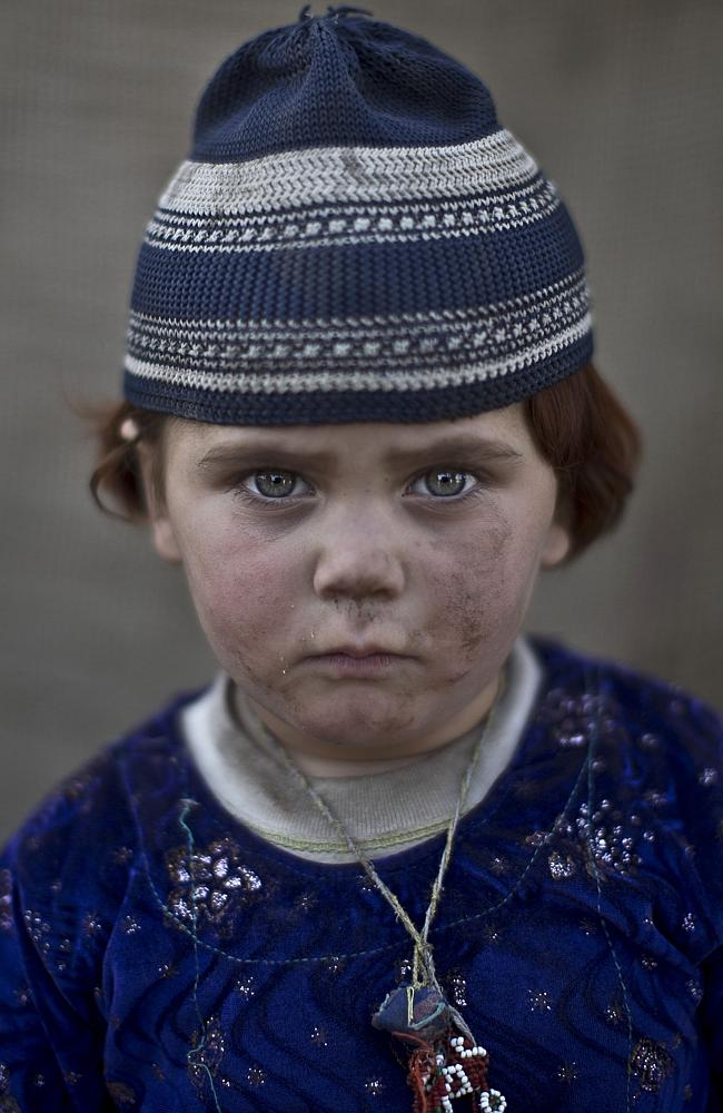 Afghan refugee girl, Basmina, 3, poses for a picture, while playing with other children in a slum on the outskirts of Islamab...