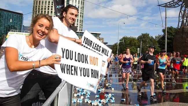 Mix 101 cheer on the runners at the drink station in Queensbridge Square, South Bank. Picture: Sarah Matray