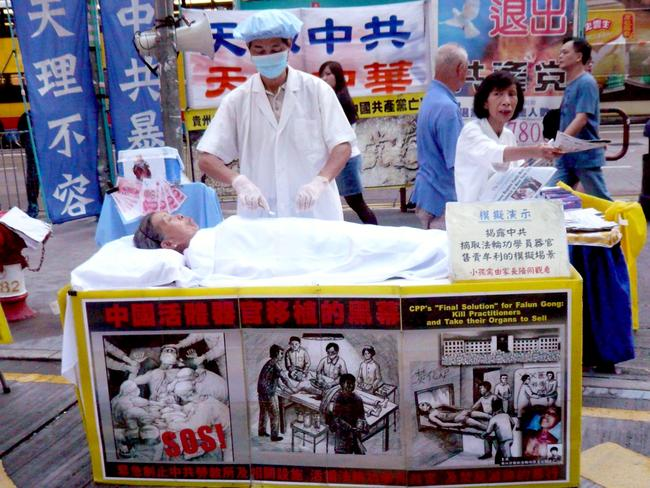A pro Falun Gong protestor simulates an 'organ harvesting' procedure in Hong Kong. Picture: Cory Doctorow/Flickr