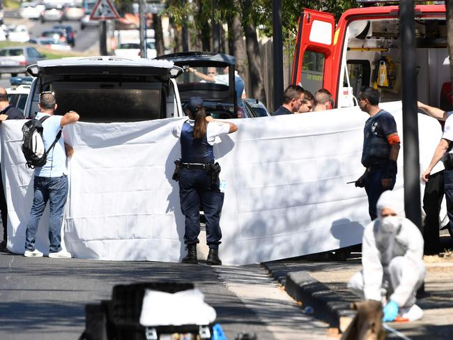 A white sheet is erected as the body of the victim is evacuated to a waiting ambulance. Picture: AFP