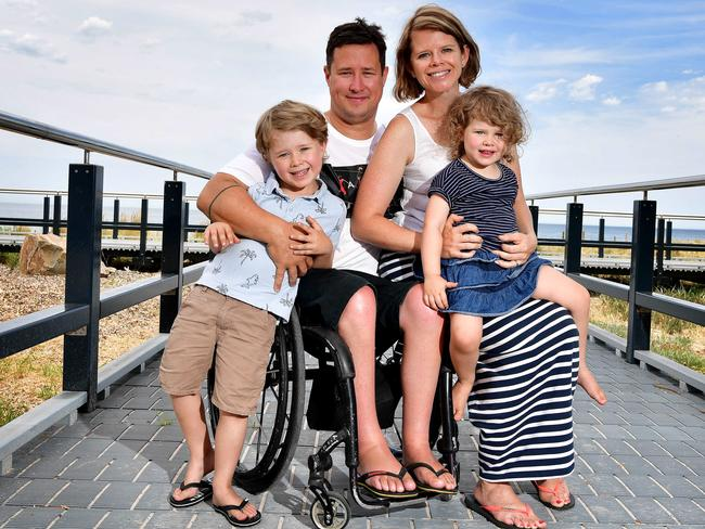 Scott Crowley with his wife and two children on a walkway by the beach. Scott is in his wheelchair and has his arms around his family