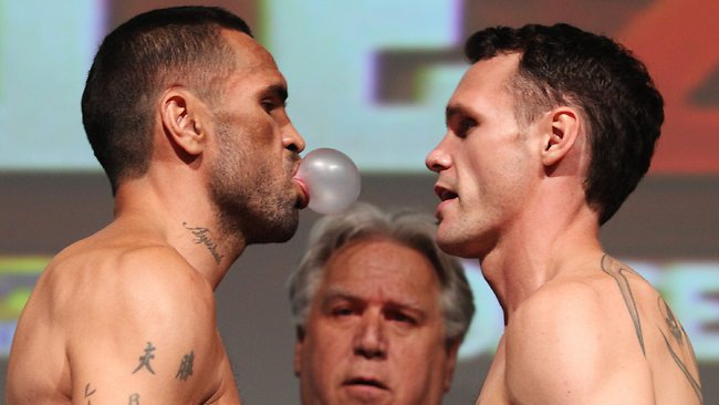 Anthony Mundine blows a bubblegum bubble in the face of Daniel Geale during the weigh-in at the Star Sports Bar ahead of their fight at the Sydney Entertainment Centre on Wednesday night. Picture: Brett Costello