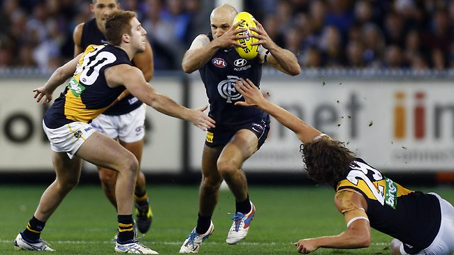 Chris Judd breaks through the tacklers.