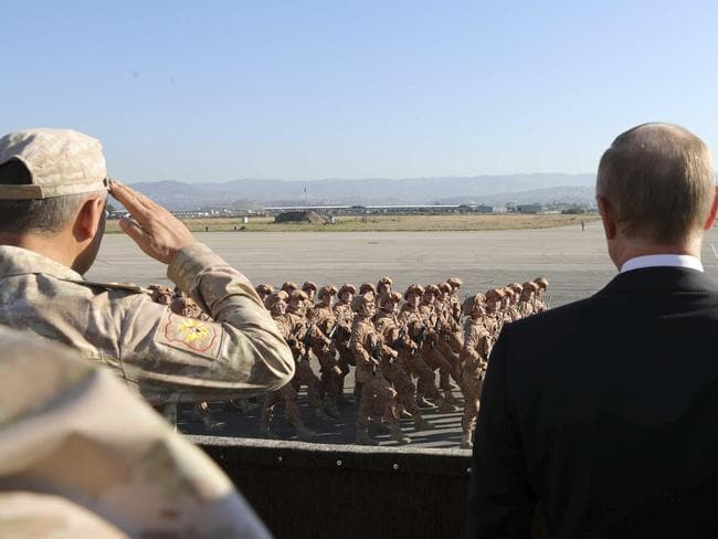 Russian President Vladimir Putin, right, watches the troops marching as he and Syrian President Bashar Assad visit the Hemeimeem air base in Syria. Private Russian military contractors were killed by a US strike in Syria, Russian media reports. Picture: AP