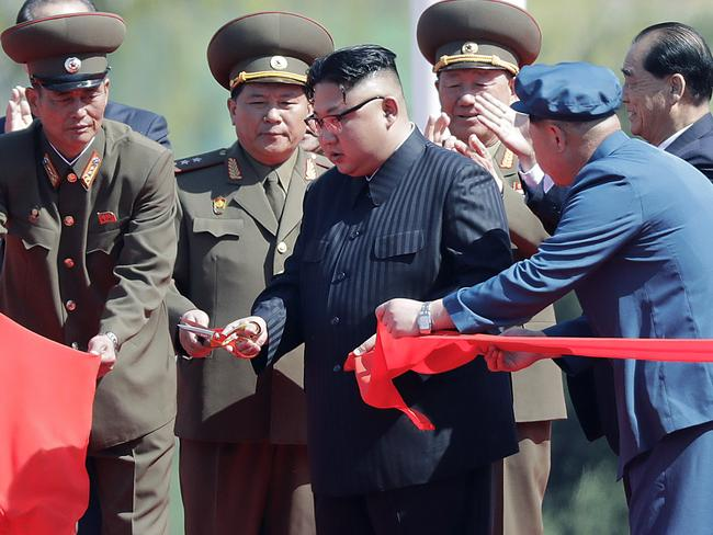 North Korean leader Kim Jong-un stands with officials as he cuts the ribbon at the official opening of the luxury apartments. Picture: Wong Maye-E/AP