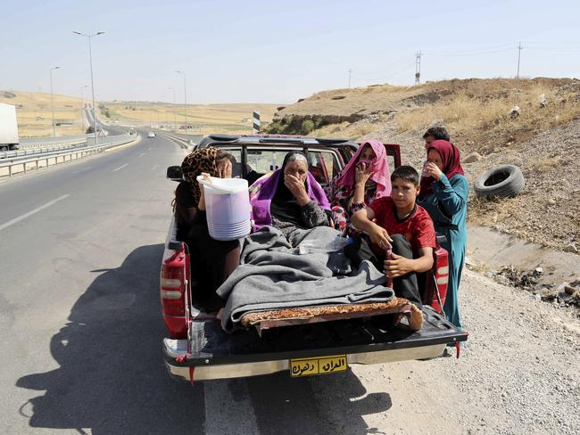 On the run ... Displaced Iraqis ride on a truck on a mountain road near the Turkish-Iraq border, outside Dahuk. The Islamic state views members of the Yazidis minority and Shiite Muslims as apostates, and has demanded Christians either convert to Islam or pay a special tax. Source: AP