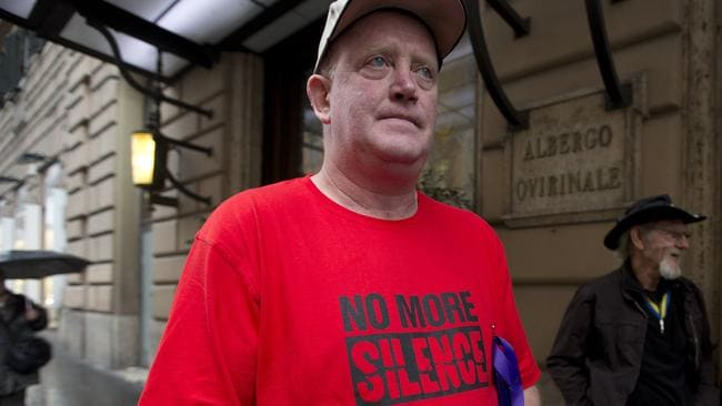 "Dominic Ridsdale, a survivor of clergy sex abuse, wears a shirt reading ""No more silence"" as he stands in front of the Quirinale Hotel in Rome. Picture: AP / Alessandra Tarantino"