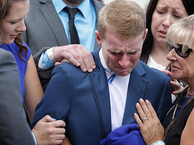 A distressed Tommy Berry is consoled by fiancee Sharnee Nisbet (blue dress) and his mum J