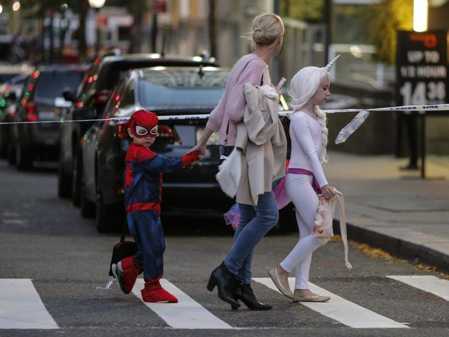 Kids in Halloween costumes cross the street near the scene where a man driving a rental truck struck and killed eight people on a jogging and bike path in Lower Manhattan. Picture: Getty