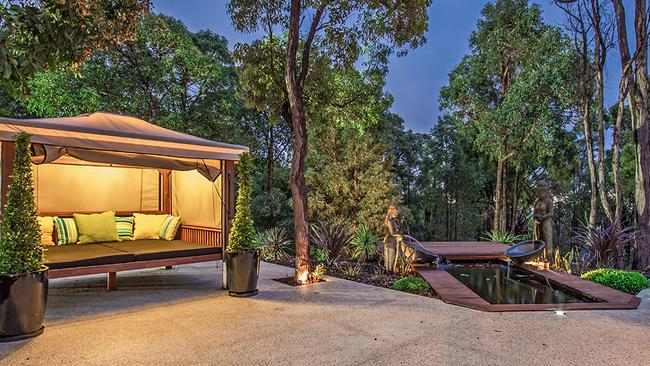 Outside is a water feature, pizza oven and Bali-bed with drop down blinds. Picture: Supplied.