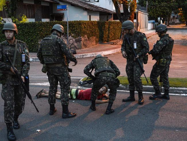Members of the Brazilian army check a man as chaos erupts across Vitoria. Picture: Gabriel Lordello/EPA
