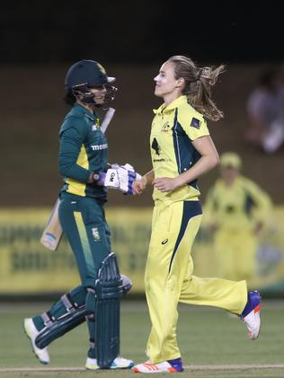 Ellyse Perry jogs past Marizanne Kapp of South Africa after capturing her wicket.