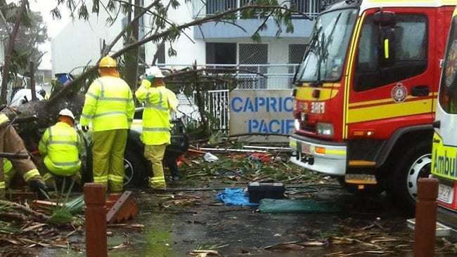 This Twitter photo from Channel 7 Bundaberg shows emergency crews working to free a man trapped in his car after a pine tree fell on the vehicle during a mini-tornado. PIC: Pippa Bradshaw/ Channel 7