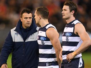 (L-R) Coach Chris Scott, Joel Selwood and Patrick Dangerfield of the Cats are seen during the national antheum during the second semi-final between the Geelong Cats and the Sydney Swans at MCG in Melbourne, Friday, September 15, 2017. (AAP Image/Julian Smith) NO ARCHIVING, EDITORIAL USE ONLY