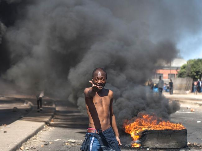 A protester shouts anti-Mugabe slogans in front of burning tyres during a demonstration in Makokoba, Bulawayo Zimbabwe. Picture: AFP/STRINGER