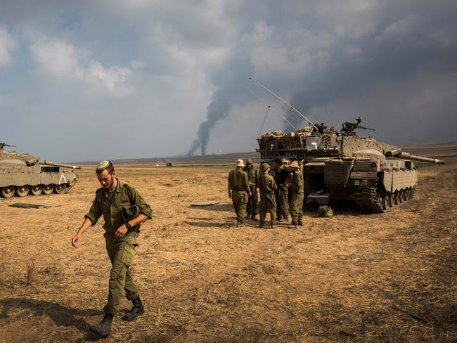 Raw power ... Israeli soldiers stand near their tank while smoke due to air strikes and shelling rises from Gaza.