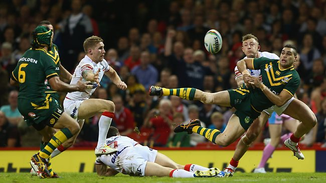 Greg Inglis of Australia passes to set up his sides first try scored by Jonathan Thurston (L) as Kevin Sinfield and Sam Tomkins of England fail to tackle during the Rugby League World Cup Group A match between Australia and England.