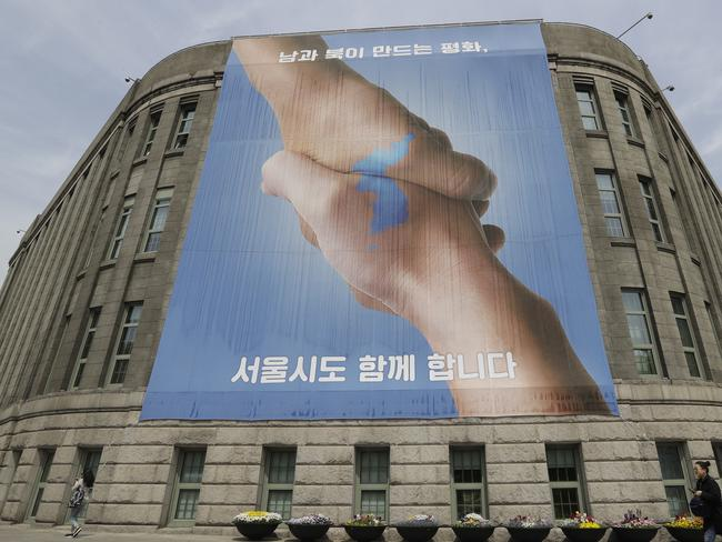 A woman walks by a banner showing a map of the Korean peninsular to wish for a successful inter-Korean summit in Seoul, South Korea. Picture: AP