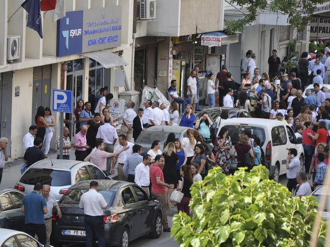 People gather outside an office building following an earthquake in the coastal city of Izmir, Turkey. Picture: Mehmet Ozdogru/Depo Photos via AP