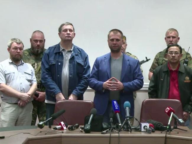 This image grab taken from an AFP TV video shows the Prime Minister of the self-proclaimed Donetsk People's Republic, Alexander Borodai (C) posing with Colonel Mohamed Sakri of the Malaysian National Security Council (2ndR) during the handing over to Malaysia of the two black boxes recovered from the crash site of the MH17 jet, at a press conference in Donetsk. Picture: AFP