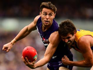 PERTH, AUSTRALIA - JULY 16: Lachie Weller of the Dockers handpasses the ball under pressure from Andrew Gaff of the Eagles during the 2017 AFL round 17 match between the Fremantle Dockers and the West Coast Eagles at Domain Stadium on July 16, 2017 in Perth, Australia. (Photo by Daniel Carson/AFL Media/Getty Images)