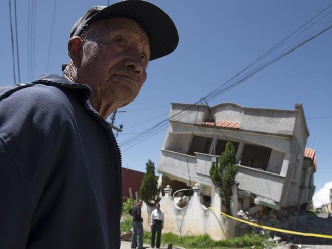 A man stands close to homes that collapsed during an earthquake in San Pedro, Guatemala, on Monday. Picture: AP Photo/Oliver de Ros