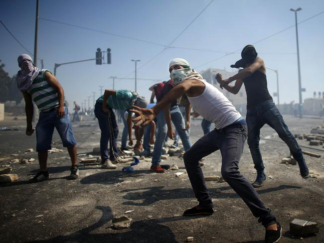 Ground force ... masked Palestinian protesters throw stones towards Israeli police. It has been almost a daily routine since 1948.