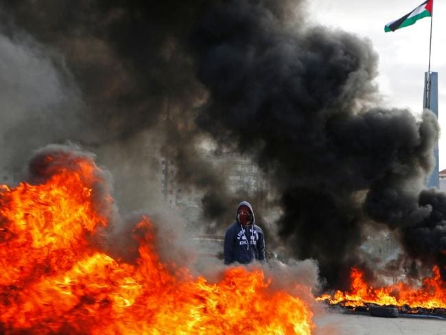 A Palestinian protester stands between burning tyres during clashes with Israeli troops at a protest against Mr Trump's decision. Picture: Abbas Momani/AFP