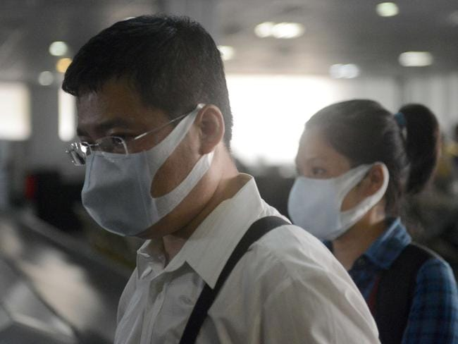 People, wearing protective face masks, stand upon arrival at the Murtala Mohammed Airport in Lagos, Nigeria. Pic: AFP.
