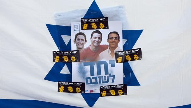 Revenge act ... Israelis hold the national flag with photos of the Israeli teens. Picture: Oded Balilty