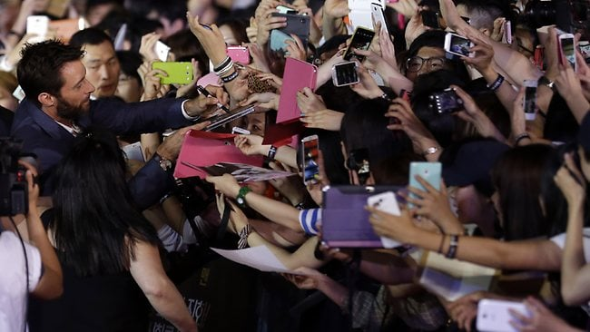 """Actor Hugh Jackman signs autographs for his fans during the premiere event of his new film """"The Wolverine"""" in Seoul. Picture: AP"""