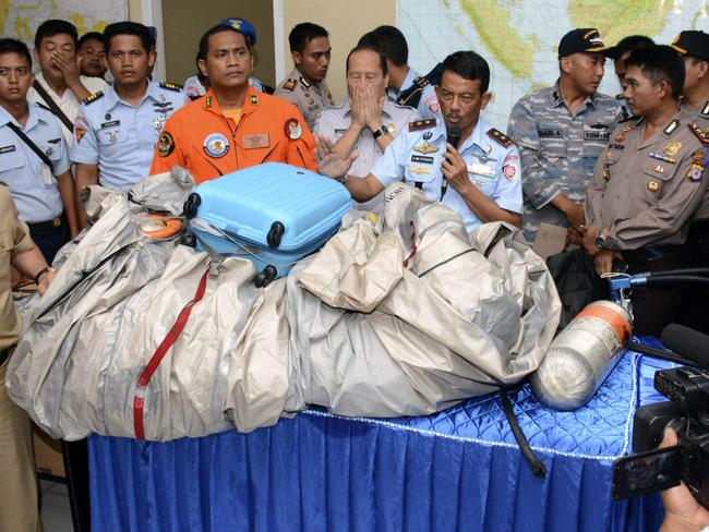 Commander of Indonesian air force 1st Operational Command Rear Marshall Dwi Putranto, centre, shows the aeroplane parts and a suitcase found floating on the water. Picture: Dewi Nurcahyani