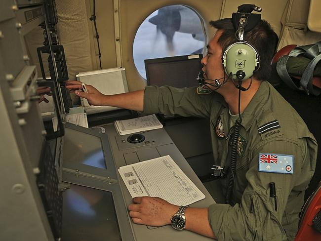 Flight Officer Jack Chen mans the navigation and comms station on board a Royal Australian Air Force AP-3C Orion as they search for debris or wreckage of missing Malaysian Airlines flight MH370.