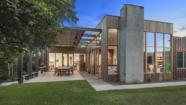 A covered outdoor entertainment area leads to a lush and established backyard.
