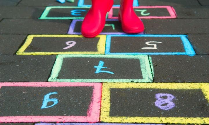Young girl is playing hopscotch