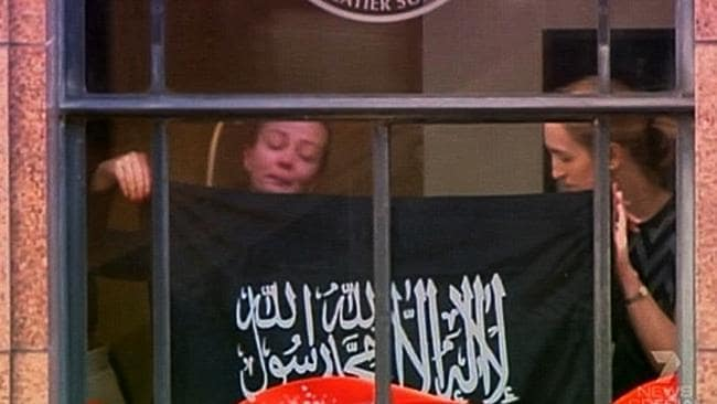 Hostages Marcia Mikhael and Katrina Dawson in the window of the Lindt Cafe during the siege.