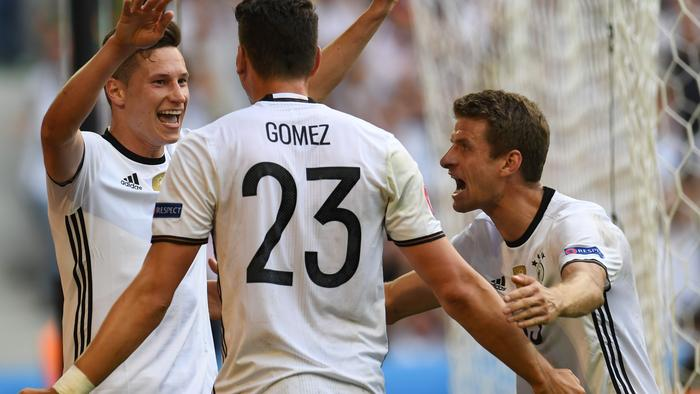 TOPSHOT - Germany's forward Mario Gomez (C) celebrates with Germany's midfielder Julian Draxler and Germany's midfielder Thomas Mueller (R) after scoring a goal during the Euro 2016 round of 16 football match between Germany and Slovakia at the Pierre-Mauroy stadium in Villeneuve-d'Ascq near Lille on June 26, 2016. / AFP PHOTO / PATRIK STOLLARZ