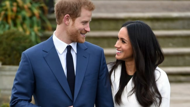 Harry stares adoringly at Meghan. Photo: Getty
