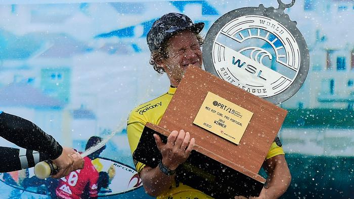 Hawaian surfer John John Florence raises the the trophy on the podium after securing the World Surf League World Title at Supertubos beach near Peniche, central Portugal, on October 25, 2016. / AFP PHOTO / FRANCISCO LEONG