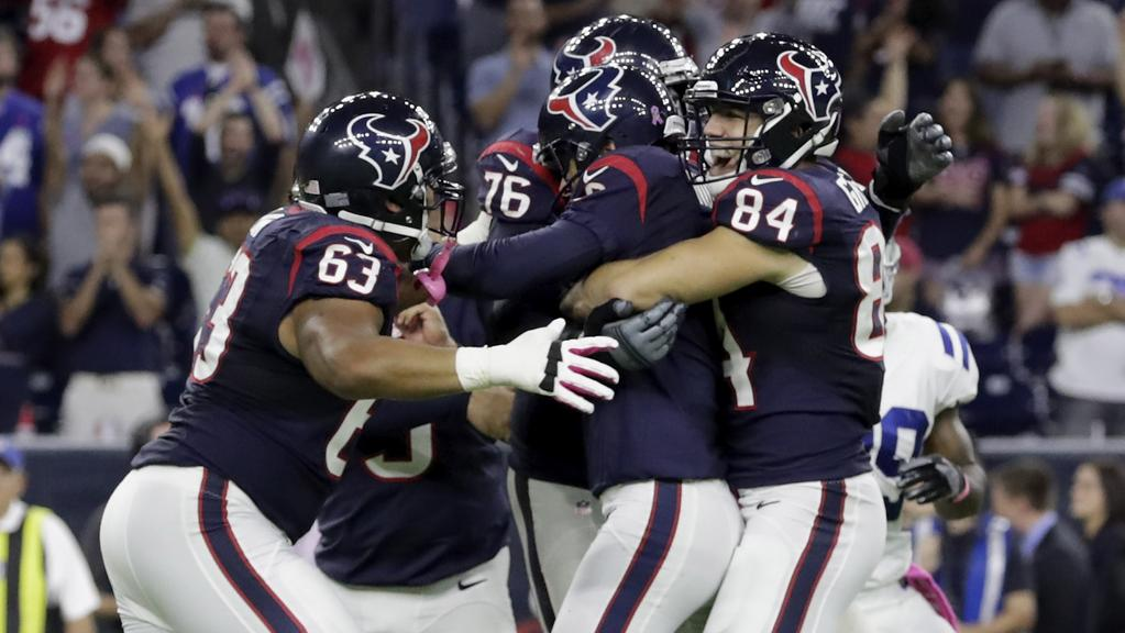 Nick Novak #8 of the Houston Texans is mobbed by Ryan Griffin #84 and Kendall Lamm #63 after kicking a 33 yard game winning field goal in overtime.