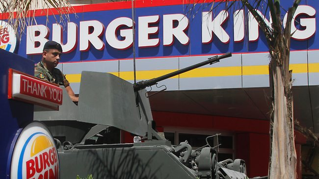 A Lebanese army soldier sits on his armored personnel carrier, as he stands guard outside the Burger King as part of stepped up security measures, in the southern port city of Sidon, Lebanon; Picture: Mohammed Zaatari