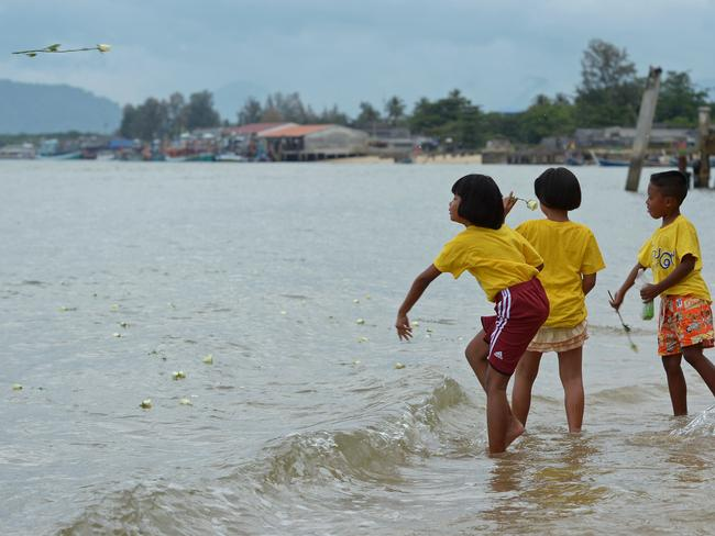 Thai children throw roses into the sea near the Ban Nam Khem tsunami memorial park as the tenth anniversary of the 2004 tsunami is remembered in Phang-nga province. Picture: AFP / Pornchai Kittiqwongsakul