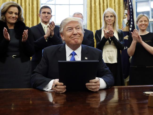 President Donald Trump smiles after signing three executive actions in the Oval Office. Picture: AP