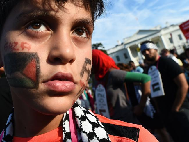 International outrage ... A young boy joins other people in a demonstration in front of the White House in Washington, DC, to protest against Israel's deadly bombing of Gaza.