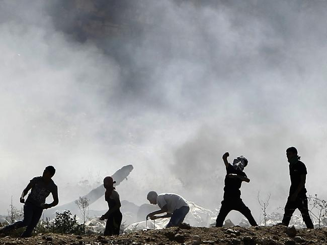 Protests ... Palestinians clash with Israeli security forces (unseen) after a demonstration in support of Gaza at the Hawara checkpoint, east of the West Bank city of Nablus.