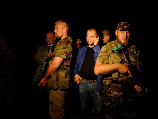 "Self-proclaimed Prime Minister of the pro-Russian separatist ""Donetsk People's Republic"" Alexander Borodai stands next to guards as he arrives on the site of the crash. Picture: AFP"
